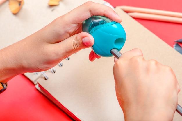 연필을 깎습니다. 수업 시간에 학교에서 아이의 손이 연필을 깎는다. 배경에는 테이블에 스케치북과 색연필이 있습니다. 빨간색 배경입니다.