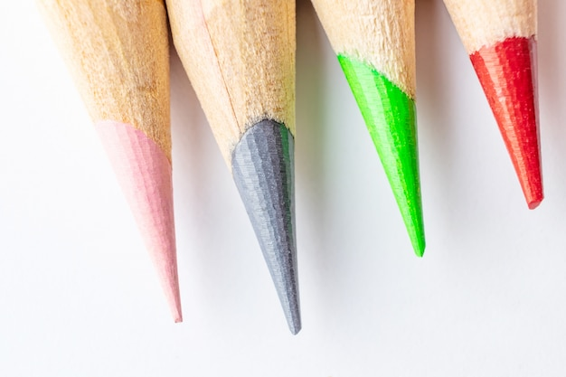 Sharpened art color pencils close up on white background.