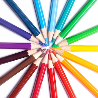 Sharpened colored pencils lie in a circle with their noses in the center, school supplies, lgbt symbol, close up.