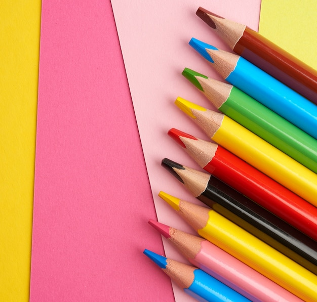 Sharpened colored wooden pencils on an abstract background of cardboard