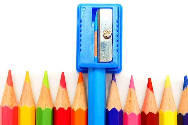 Sharpener and pencils on a white table.