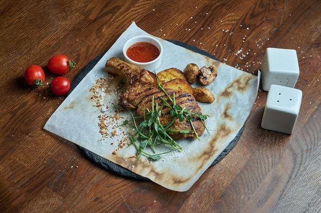 Большая порция жареного шашлыка. филе свинины, стейк на косточке, приготовленный на гриле с разными соусами и свежими овощами. shashlic. вид сверху на пищевое мясо.
