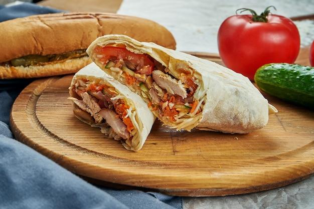 食欲をそそるshaurmaまたは肉、トマト、キャベツとshawerma。鶏肉。木製トレイのケバブ。クローズアップ、セレクティブフォーカス