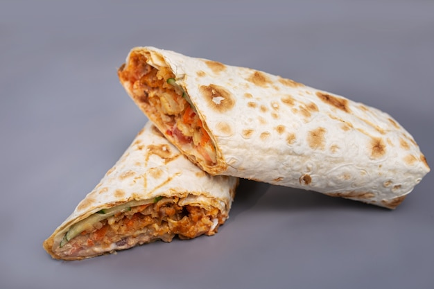 Shaurma with chicken and vegetables on a gray surface.