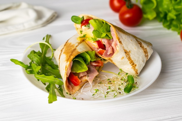 Shaurma wrapped sandwich with lettuce tomatoes ham and cheese on a white plate