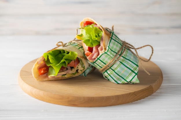 Shaurma wrapped sandwich with lettuce tomatoes ham and cheese on a wooden plate