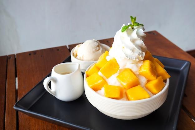 Ледяной бритый десерт с нарезанным манго. подается с ванильным мороженым и взбитыми сливками.