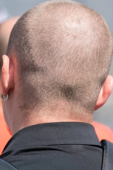 A shaved man on the back of his head. the round head of an adult male from behind.
