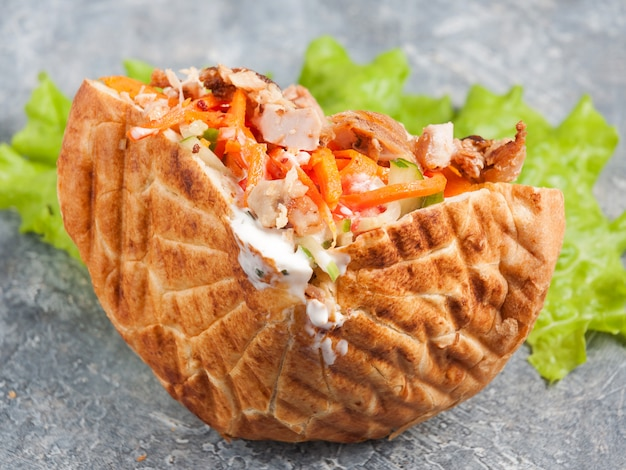 Shaverma in pita or pita bread with chicken fillet and vegetables Premium Photo