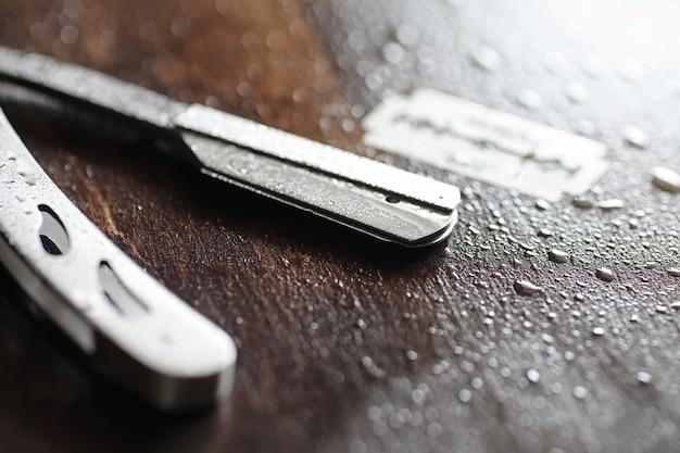 Аксессуары для бритья на деревянном фоне текстуры и одноразовые лезвия