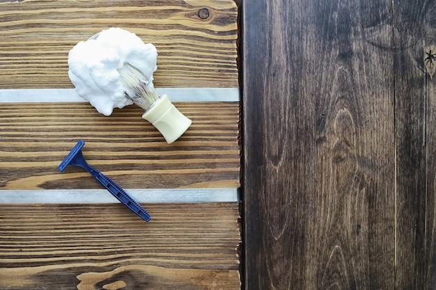 나무 질감 배경에 면도 액세서리입니다. 도구. 일회용 면도기, 브러시, 거품 및 위험 면도기.