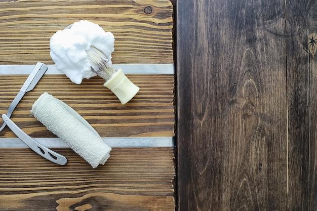 木製のテクスチャ背景のシェービングアクセサリー。ツール。使い捨てシェービングマシン、ブラシ、フォーム、ハザードカミソリ。