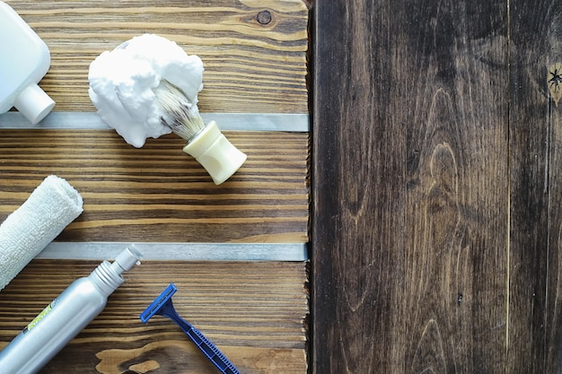 Shaving accessories on a wooden texture background. tools. disposable shaving machine, brush, foam and hazard razor.