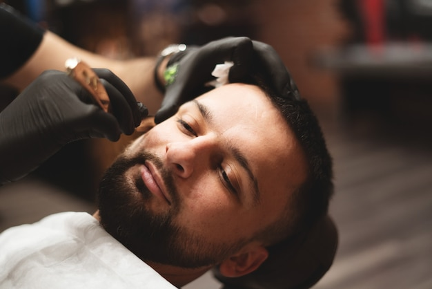 Shaving a beard in a barbershop with a dangerous razor.