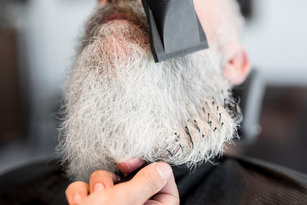 Shaving beard of senior client in barbershop
