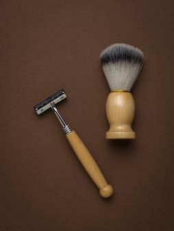 Кисть для бритья и бритва с деревянной ручкой на коричневом фоне. мужские аксессуары для ухода за внешностью. плоская планировка.