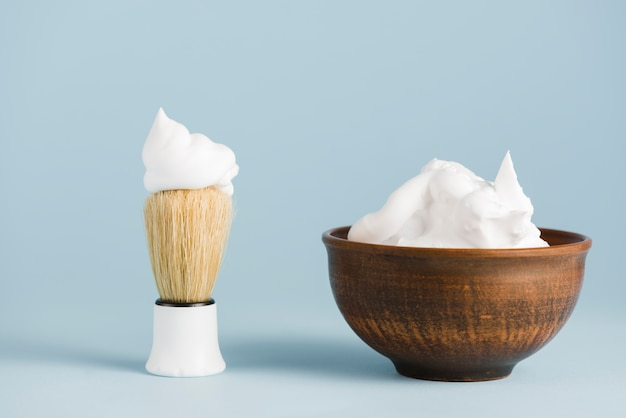 Shaving brush and bowl of foam against blue background