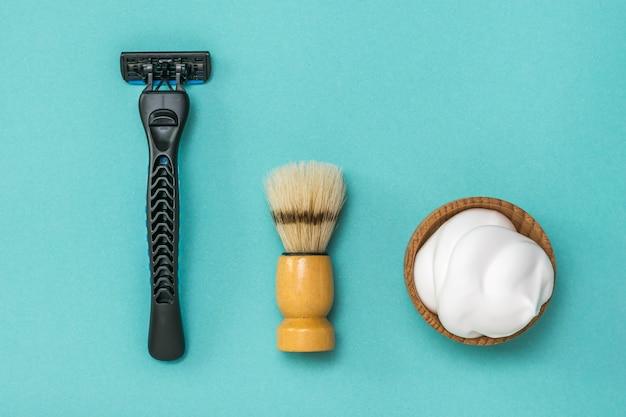 Кисть для бритья, бритва и пена для бритья на синем фоне. набор для ухода за мужским лицом. плоская планировка.