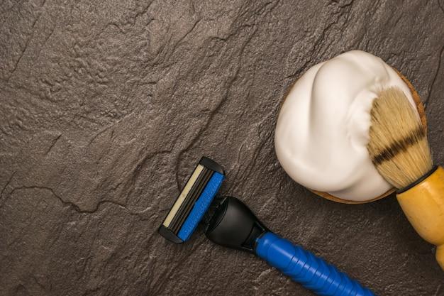 茶色の石の背景に泡と青い男性用かみそりでシェービングブラシ。男の顔のケアのために設定します。フラットレイ。