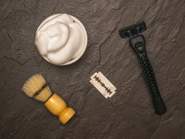 짙은 돌 배경에 나무 손잡이가 있는 면도 거품, 면도기, 면도 브러시. 남자의 얼굴 관리를 위해 설정합니다. 플랫 레이.