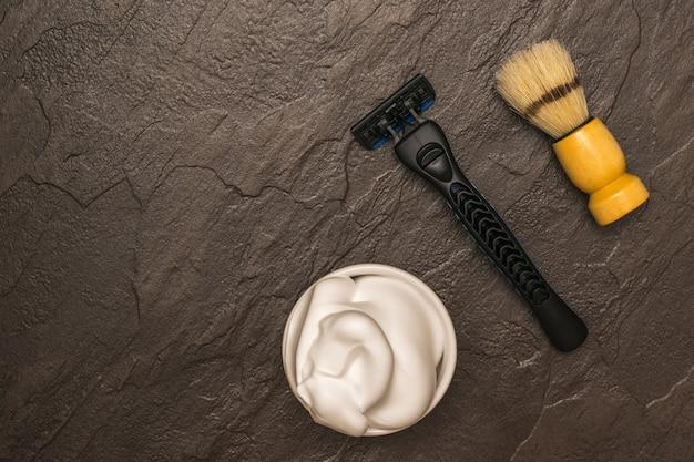 石の背景に木製のハンドルが付いたシェービングフォーム、シェービングマシン、シェービングブラシ。男の顔のケアのために設定します。フラットレイ。