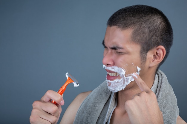 Shaving handsome guy shaved on the face on gray
