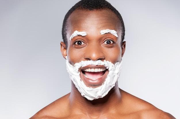 Бритье - это весело. портрет игривого африканца с кремовой бородой и усами для бритья, улыбающегося в камеру, стоя на сером фоне