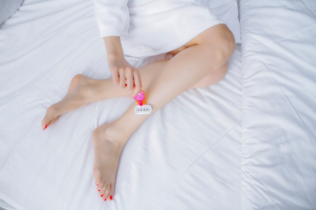 Shaving legs with a razor on a white background. the girl shaves her legs. depilation of the legs with a razor.