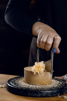 Бритье сыра тет-де-муан с помощью ножа girolle. голова монаха. разновидность швейцарского полутвердого сыра из коровьего молока.