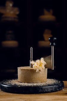 ジロールナイフを使用してテトドモワンチーズを剃る。僧侶の頭。牛乳から作られたさまざまなスイスのセミハードチーズ。