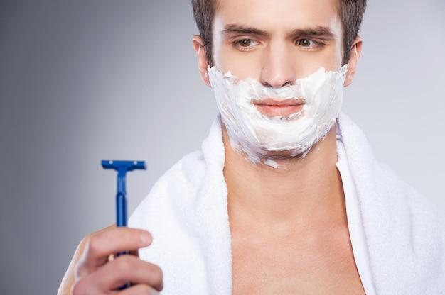 Бритье плохой бритвой. молодой человек без рубашки смотрит на бритву и выражает негатив, стоя изолированным на сером фоне