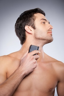 Shaving with electric shaver. cropped image of handsome young man shaving his face with electric shaver while standing isolated on grey background