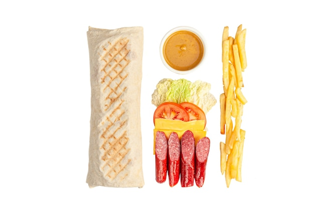 シャワルマと材料。レタス、トマト、スモークソーセージ、チェダーチーズ、フライドポテトが含まれています。ソースのボウル。白色の背景。上からの眺め。
