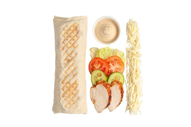 シャワルマと材料。組成には、レタス、トマト、キュウリ、鶏の切り身、チーズが含まれます。ガーリックソースのボウル。白色の背景。上からの眺め。