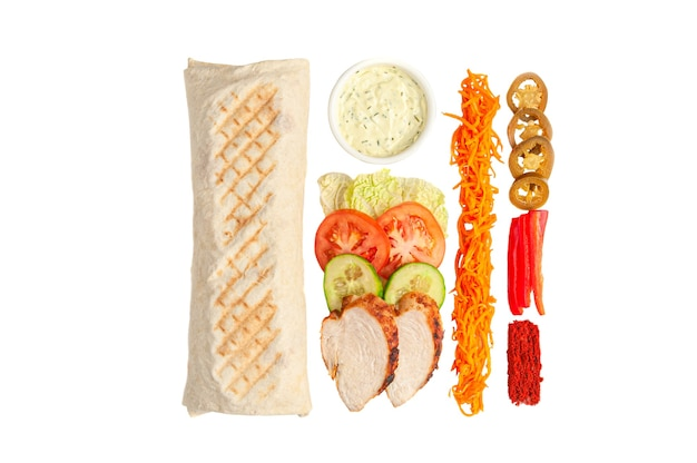 Шаурма и ингредиенты. в состав входят: салат, помидор, огурец, куриное филе, перец халопено, маринованная морковь, перец и специи. чаша с соусом. белый фон. вид сверху.
