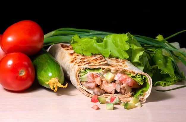 Аппетитная шаурма из лаваша, жареной говядины, свежих овощей и сыра на деревянном фоне