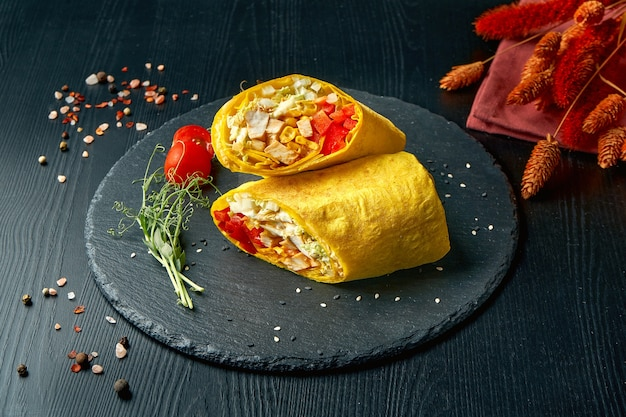 Shawarma or burrito roll with tomatoes, lettuce, chicken and corn. street food Premium Photo