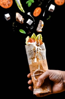 Shawarma chicken pita roll in hand with ingredients flying in the air