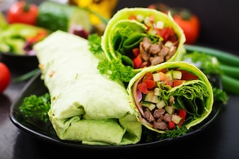 Shawarma from juicy beef, lettuce, tomatoes, paprika and onion in pita bread