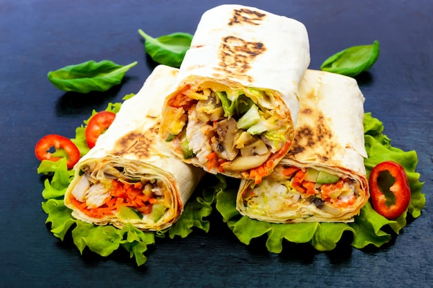 Shawarma from lavash (pita), stuffed with chicken, mushrooms, vegetable, sauce