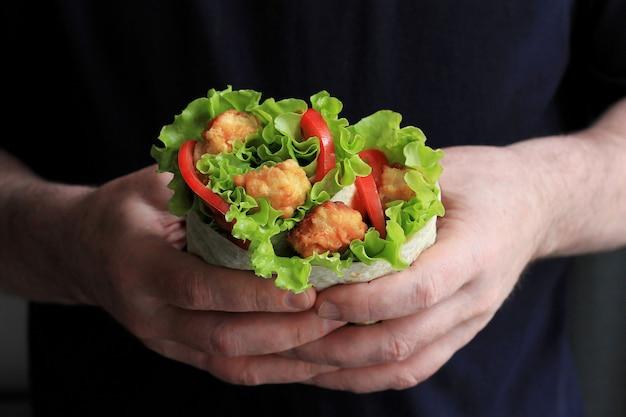 남자 손에 shawarma입니다. 도너 케밥. 고기, 양파, 샐러드, 토마토와 함께 shawarma.