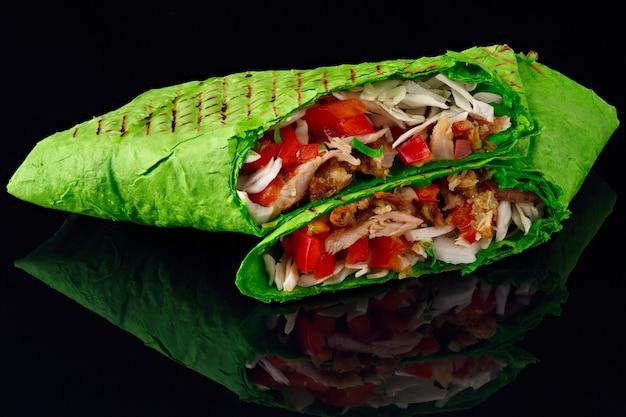 피타 빵의 shawarma가 잘리고 검정색 반사 배경에 놓여 있습니다.