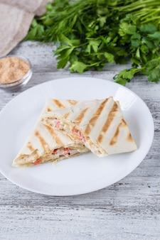 白いプレートに鶏肉と野菜を添えた薄いピタパンのシャワルマ