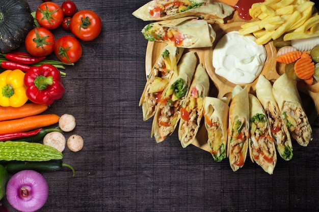 Shawarma made from chicken, turkey, beef, veal, or mixed meats on black wooden table