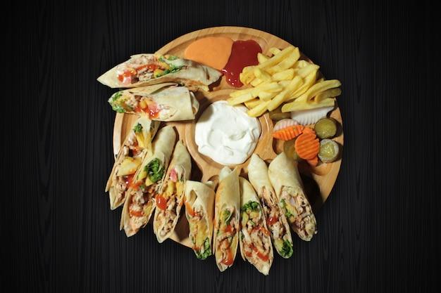 Шаурма из куриного мяса, индейки, говядины, телятины или смешанного мяса на черном деревянном столе