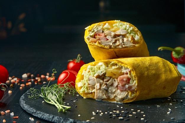 Шаурма или рулет из буррито с листьями салата, курицей и огурцом в желтой лаваше. уличная забегаловка. копировать пространство