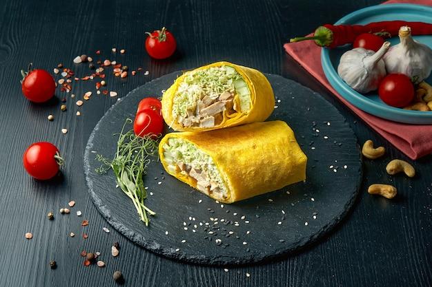 Шаурма или рулет из буррито с листьями салата, курицей и огурцом в желтой лаваше. уличная забегаловка