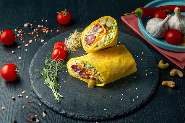 Шаурма или рулет из буррито с листьями салата, с копчеными колбасами и яйцом в желтой лаваше. уличная забегаловка