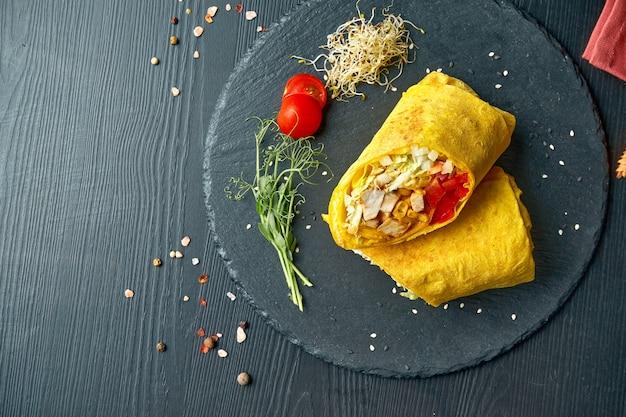 Шаурма или рулет из буррито с помидорами, листьями салата, курицей и кукурузой. уличная забегаловка