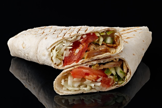 Shawarma in pita bread is cut and lies on a black reflective background